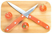 Crossed knives on chopping board — Stock Photo