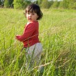 Stock Photo: Little girl standing in high grass