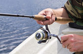 Fisherman rotating fishing reel — Stock Photo
