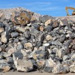 Stock Photo: Excavator on rock pile