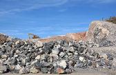 Excavator on rock pile — Stockfoto