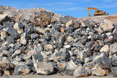 Excavator on rock pile — Stockfoto