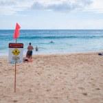 Oahu Hawaii - Warning no swimming sign, Sandy beach — Stock Photo #12582097