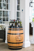 Wine bottles on wooden barrel — Stock Photo
