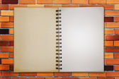 Notebook on the red brick background — Stock Photo