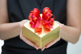 Golden gift box with red and orange satin bow on hand — Stock Photo