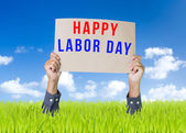 Happy labor day cardboard with man hand over green field and blue sky background — Stock Photo