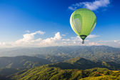 Colorful hot air balloon over the mountain — Stock Photo