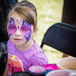 Young girl with butterfly face paint — Stock Photo