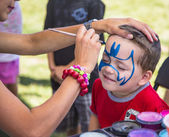 Young boy getting blue face paint — Stock Photo