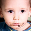 Little baby after eating chocolate cookie — Stock Photo #12360211