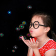 Happy girl play with soap bubbles isolated black background — Stock Photo #28035111