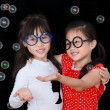 Two happy girl play with soap bubbles isolated black background — Stock Photo #28035569
