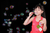 Happy girl play with soap bubbles isolated black background — Stock Photo
