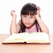 Serious little girl reading a book — Stock Photo