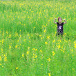 Portrait of beautiful happy little girl in a field of yellow flo — Stock Photo