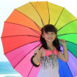 girl with colorful umbrella on the sandy beach — Stock Photo
