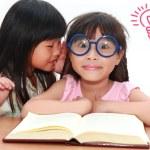 Cute little asian girl whispering something to her sister — Stock Photo