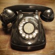 Постер, плакат: Old telephone with rotary dial on old wooden