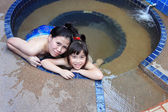 Adorable girl and her mother in hot spring water pool — Stock Photo