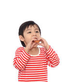 Little cute kid eating eating cookie — Stock Photo