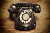 Old telephone with rotary dial on old wooden — Stock Photo