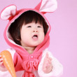 Baby dressed in Easter bunny ears with carrot — Stock Photo #28119877