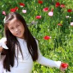 Smiling asian little girl with long dark hair on poppy field — Stock Photo #28125593