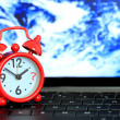 Red alarm clock on keyboard with earth background. When the end — Stock Photo #28135923