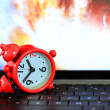 Red alarm clock on keyboard with earth boom background. — Stock Photo #28135961