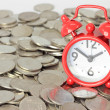 Red clock staying on coins. Time is money concept — Stock Photo #28137435