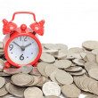 Red clock staying on coins. Time is money concept — Stockfoto