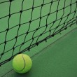 Tennis ball on court and net — Stock Photo