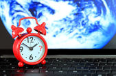 Red alarm clock on keyboard with earth background. When the end — Stock Photo