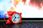 Red alarm clock on keyboard with earth boom background. — Stock Photo