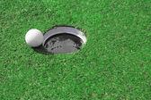 Golf ball go to the hole — Stock Photo