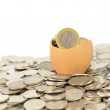 Stock Photo: Broken eggshell on coins