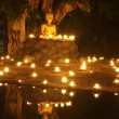 Buddha statue reflect on water with candles fire lighting — Stock Photo