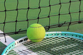 Tennis ball and racket on tennis court — Stock Photo