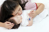 Sick child in her mother's arms. — Stock Photo