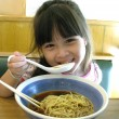 Asian young girl eating noodle — Stock Photo