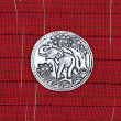 Elephant metal plate on red cotton handmade — Stock Photo