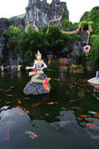 Mermaid statue thai style on the lake with carp fish — Stock Photo