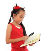 Beautiful little asian girl reading book with magnifying glass — Stock Photo