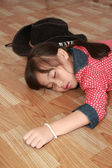 Young cowgirl sleeping on the floor — Stock Photo
