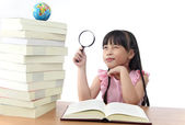 Student little girl reading with magnifying glass — Stock Photo