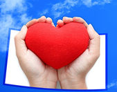 Red heart symbol on hands blue sky background — Stock Photo