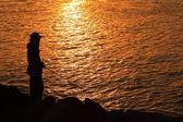 Silhueta de pescador ao pôr do sol — Fotografia Stock