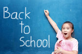 Girl drawing back to school on chalkboard — Stock Photo