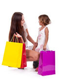 Mother and daughter shopping carrying bags — Stock Photo